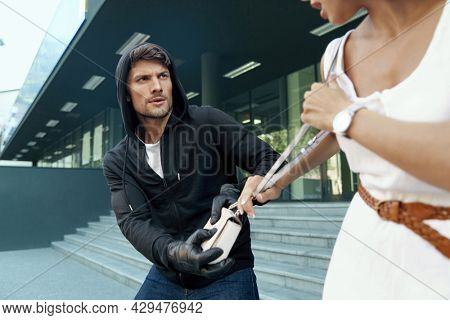 Aggressive robber want to steal handbag of scared girl. European male bandit wear black hoodie and gloves. Woman wear white dress. Concept of robbery. City daytime