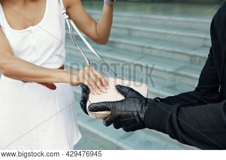 Robber want to steal handbag of girl. Partial image of bandit wear black hoodie and gloves. Woman wear white dress. Concept of robbery. City daytime