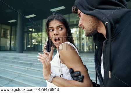 Angry robber grabbing hand of frightened girl. Young woman wear white dress and hold mobile phone. Male bandit wear black hoodie and gloves. Concept of robbery and kidnapping. City daytime