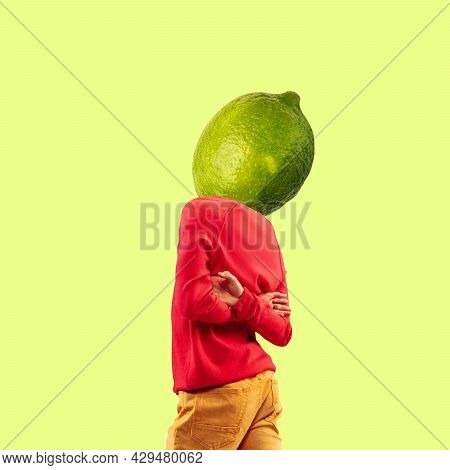 Surrealism. One Young Man In Retro Style Clothes Headed With Lime Over Yellow Background. Creative I