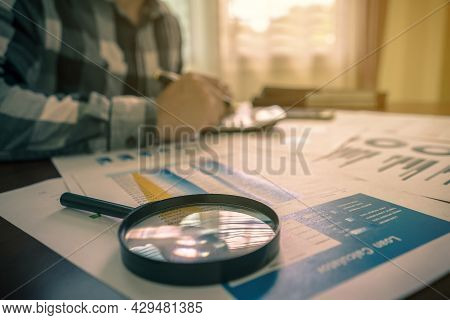 Auditors Are Calculating And Verifying Account Finance With A Magnifying Glass, Paper Reports, Stati