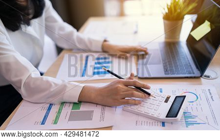 Office Worker Or Business Women Using Calculator, Laptop Computer, And Chart Report Paper, Statistic