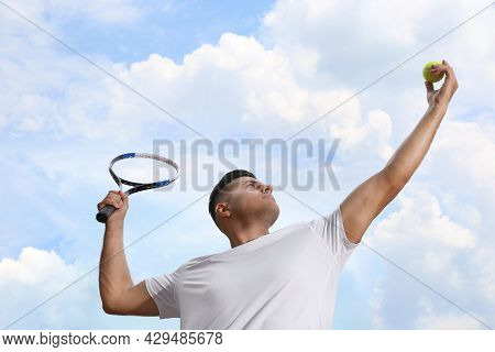 Man Serving Ball While Playing Tennis Outdoors, Low Angle View