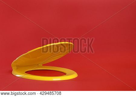 New Yellow Plastic Toilet Seat On Red Background, Space For Text