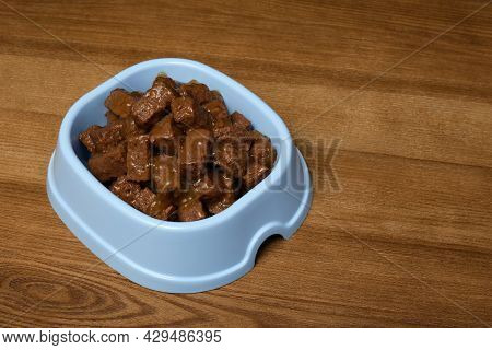 Wet Pet Food In Feeding Bowl On Wooden Background, Space For Text