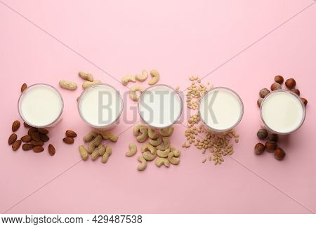 Different Vegan Milks And Nuts On Pink Background, Flat Lay