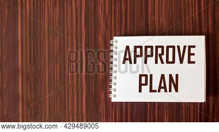 Approved Plan. The Text Approved Plan Is Written In A Notebook On A Wooden Background.