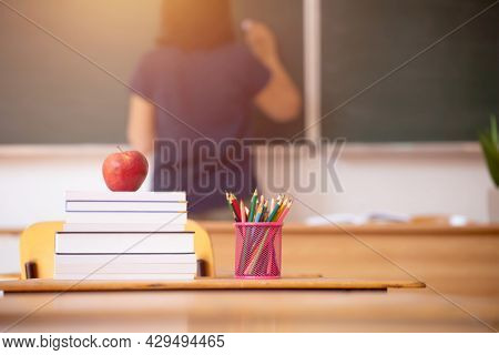 Back to School Concept. Apple, accessories and books in the classroom, chalkboard and teacher teaching in the background.