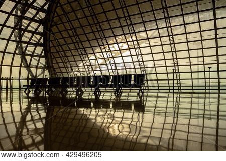 Silhouette Metal Structure Of Modern Building Architecture And Empty Waiting Chairs With Warm Sunlig