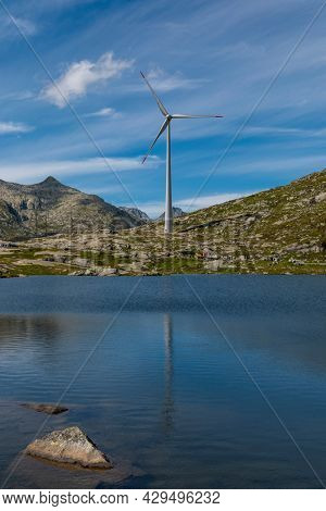 Wind turbine at the top of the Gotthard pass in the Swiss Alps is reflected in the water of the lake. Copy space for renewable energy.