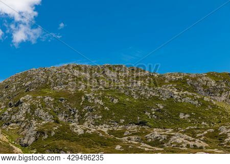Panorama from the Gotthard pass in Ticino of the Swiss Alps on a summer's day with sunshine and blue skies. Nobody inside, copy space