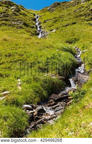 Small water spring in the meadow of the Swiss Alps mountains on the Gotthard pass. copy space