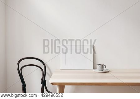 Breakfast Still Life Scene. Cup Of Coffee, Books And Empty Horizontal White Picture Frame Mockup On