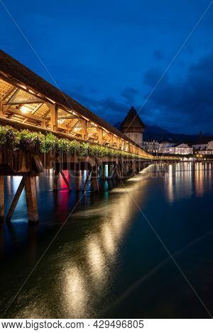 Kapellbrücke, medieval bridge in Luzern at night. The bridge is illuminated, the lights are reflected in the lake. Impressive view of the city