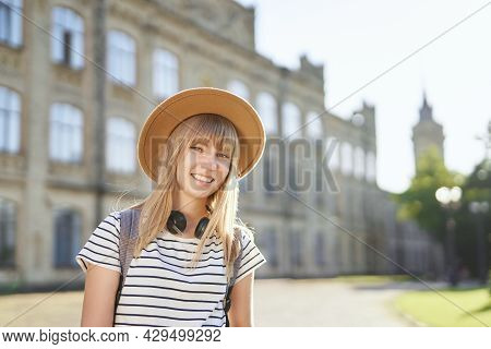 Cheerful Smiling Young Blonde Female European University Or College Student Wearing Brown Hat In Cam