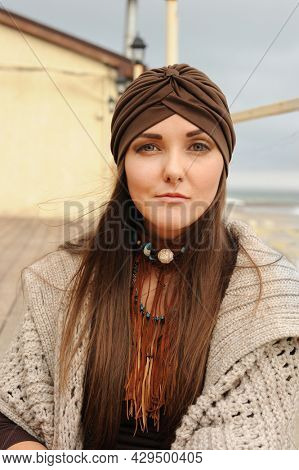 Beautiful brunette woman portrait, looking at camera and dressed in jersey turban, autumn authentic fashion concept