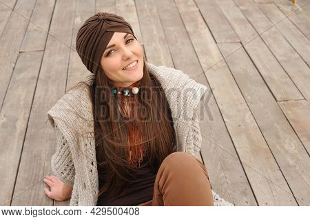 Happy smiling brunette woman portrait, looking at camera and dressed in jersey turban, autumn authentic fashion concept