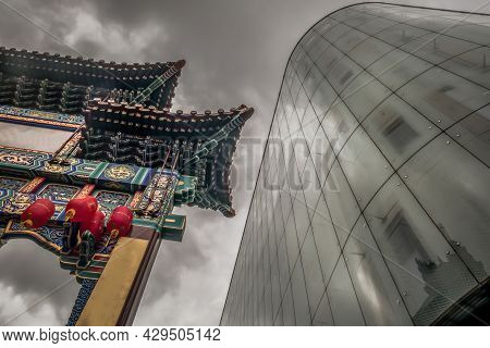 Contrast Of Modern Glass Building With Chinatown Entrance Gate In Traditional Chinese Design. Select