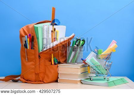 Orange School Backpack Full Of School Supplies And A Supermarket Basket With Office Supplies On A Bl