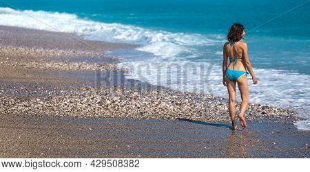 A Girl In A Swimsuit Walks Along The Beach And Looks At The Sea, Sea Waves And The Blue Sky, A Woman