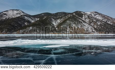 Cracks, Snow Spots, Hummocks Are Visible On The Blue Ice Of The Frozen Lake. The Wooded Slopes Of Th