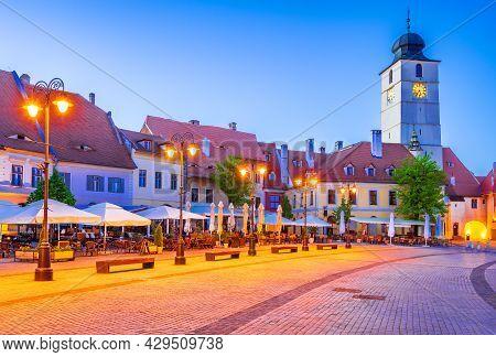 Sibiu, Romania. Twilight Image Of Council Tower In Small Square, Saxon Sight Of Transylvania.