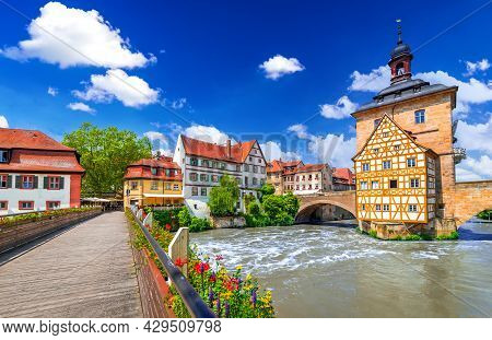 Bamberg, Germany. Half-timbered Town Hall And Regnitz River, Old Buildings And Bridge Decorated By F