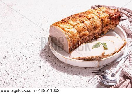 Baked Pork Loin On A Ceramic Stand With Cutlery