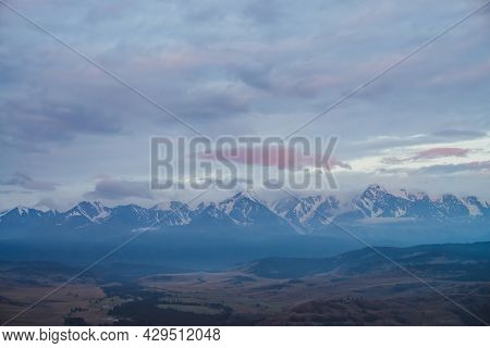 Scenic Dawn Mountain Landscape With Great Snowy Mountain Range Under Lilac Clouds. Atmospheric Color