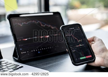 Stock Investors Hold A Phone, Open A Stock Chart Viewer To Read Stock Price Charts, Analyze Purchase