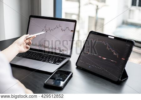 A Stock Investor Holding A Pen Pointing To A Laptop Screen Opens A Stock Chart Program To Read Stock