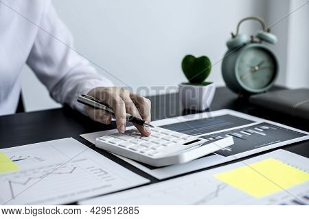 A Close-up Woman Accountant Pressing A Calculator While Holding A Pen, Using A Calculator To Calcula