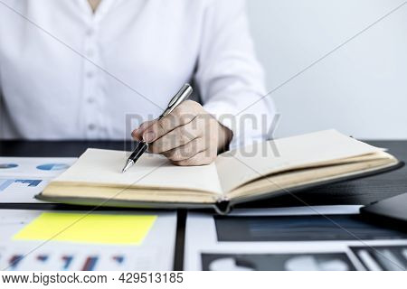 A Woman Is Writing A Memo In Her Notebook, She Is Reviewing The Company Financial Information And Wr