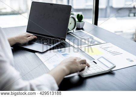 A Woman Uses A Laptop And Presses A White Calculator, She Is A Company Auditor, She Checks Documents