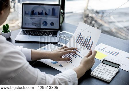 A Woman Holding A Sales Summary, The Sales Manager Is Looking At The Monthly Sales Summary Document