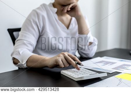 A Businesswoman Is Pressing A White Calculator, She Is Calculating The Numbers On The Company Financ