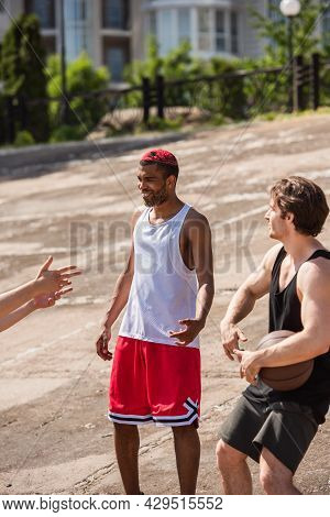 Smiling Interracial Men With Basketball Ball Talking Outdoors At Daytime.