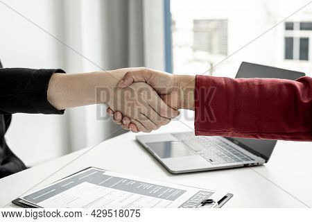The Job Interviewer And The Job Applicant Are Holding Hands After The Job Interview Is Finished. The