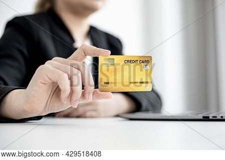 A Business Woman Holds A Credit Card To Make Payments On The Website Where She Is Shopping Online. C
