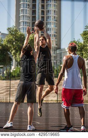 Sportsman With Basketball Ball Jumping Near Interracial Sportsmen Outdoors.