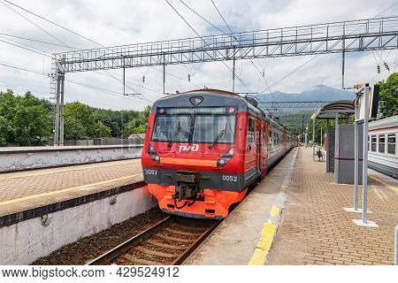 A Suburban Electric Train Of The Russian Railways Company Stands At A Railway Station In A Mountaino