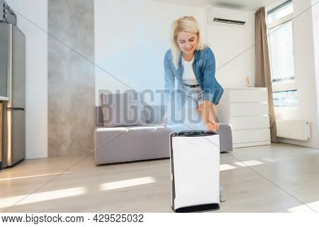 Attractive Woman With Air Purifier In The Modern Home.