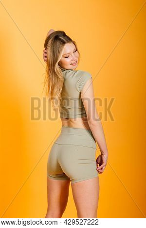 Studio Photo Of Young Caucasian Female Athlete. Slim Blonde Woman Wearing Sportwear