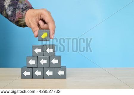 Wooden Block With Yellow Arrow Facing The Opposite Direction. Think Different, Unique, Individual An