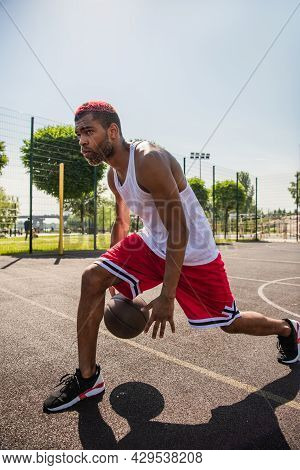 African American Sportsman Playing Basketball On Playground At Daytime.