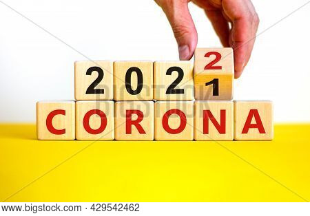 Symbol Of Covid-19 Pandemic In 2022. Doctor Turns A Wooden Cube And Changes Words 'corona 2021' To '