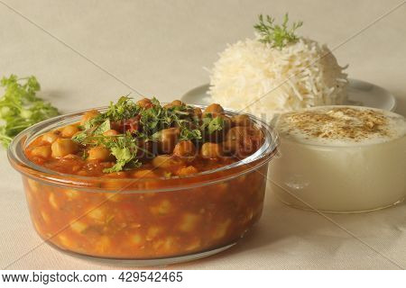 Chickpea In A Thick Gravy Of Onions Tomatoes And Spices. Served With Hot Steamed Rice And Spiced Cur
