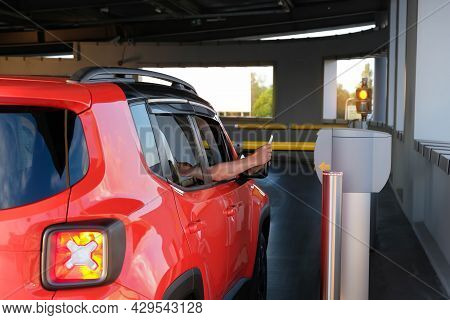 A Man Takes A Parking Ticket At The Entrance To A Paid Underground Parking Lot For A Car. Parking Se