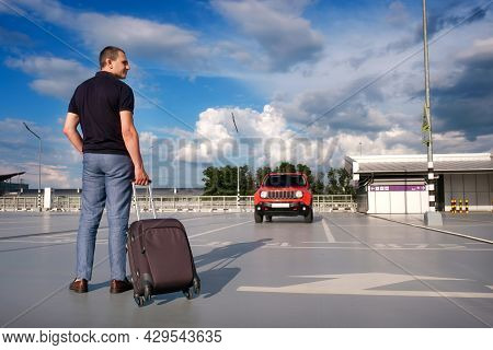Man With A Suitcase In His Hand In An Open Parking Lot. The Concept Of Travel