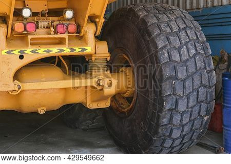 Giant Wheel Tire Of Huge Industrial Mining Truck On Repair Station. Wheel Of Yellow Auto Dumper Afte